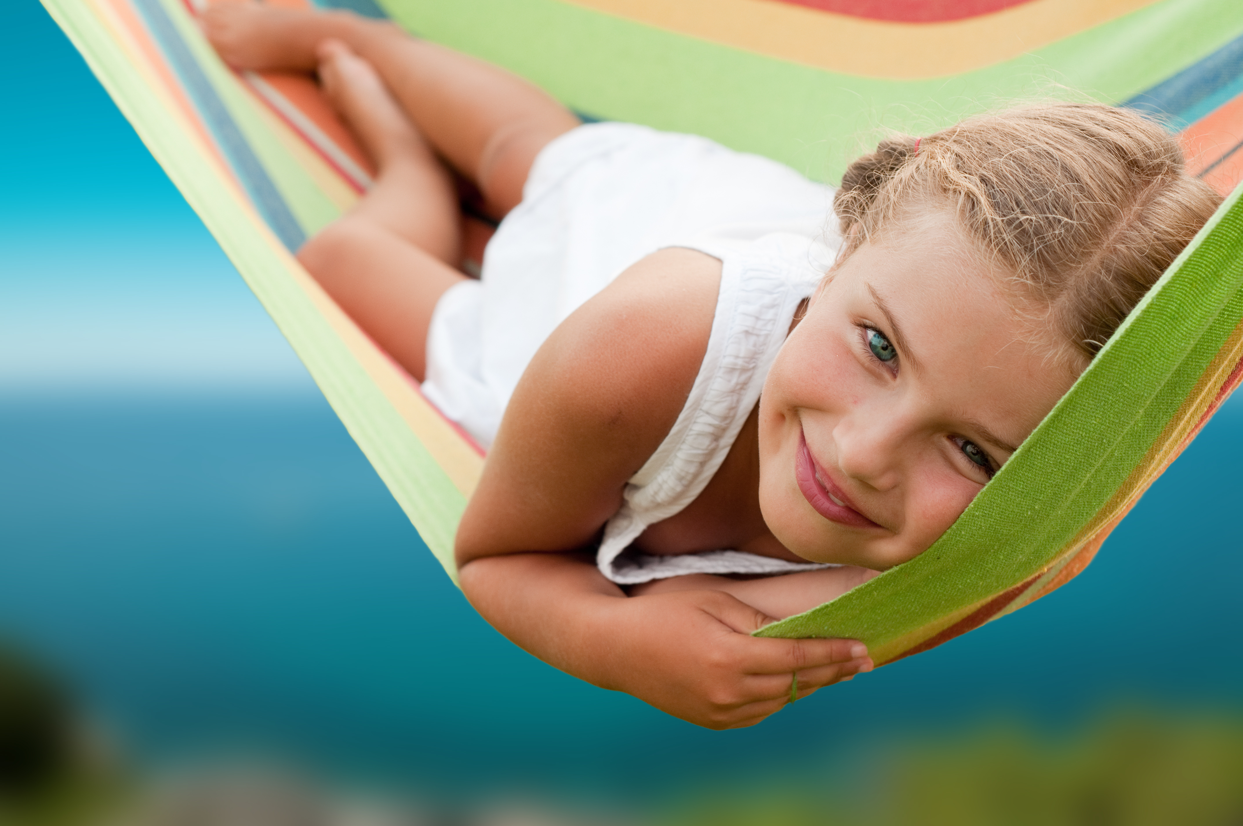 Summer vacation - Lovely  girl resting in colorful hammock